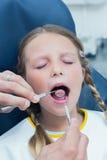 Fermez-vous de la fille faisant examiner ses dents images libres de droits