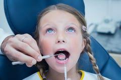 Fermez-vous de la fille faisant examiner ses dents photographie stock