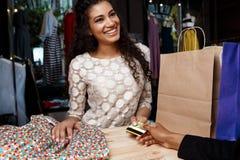 Fermez-vous de la fille payant des achats dans le centre commercial Photos libres de droits