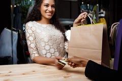 Fermez-vous de la fille payant des achats dans le centre commercial Photo stock