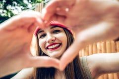 Fermez-vous de la fille de sourire avec la peau saine montrant le signe d'amour photos stock