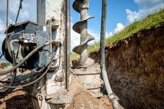 Fermez-vous de la foreuse, plate-forme de forage industrielle faisant un trou images stock