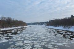 Fermez-vous de la glace cassée en rivière débordante images stock