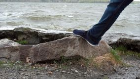 Fermez-vous de la jambe des jeans de port d'un homme se tenant sur une roche en rivière Espadrilles faisant un pas sur une pierre Image stock