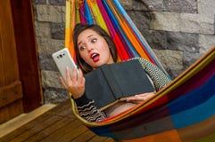 Fermez-vous de la jeune belle femme étonnée détendant dans un hamac et prenant un selfie avec son comprimé tandis que tient a Image stock