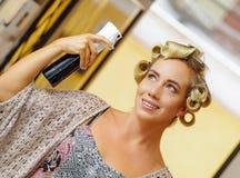 Fermez-vous de la jeune coiffure blonde de fixation de femme avec la laque dans le salon de beauté de coiffure, à un arrière-plan Photos libres de droits