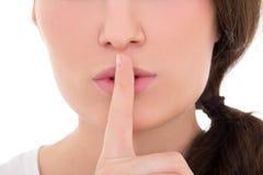 Fermez-vous de la jeune femme avec le doigt sur des lèvres d'isolement sur le blanc Image libre de droits