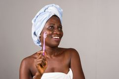 Fermez-vous de la jeune femme heureuse avec la brosse à dents sur le fond gris photo libre de droits