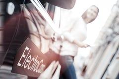 Fermez-vous de la jeune femme louant la voiture électrique Image libre de droits