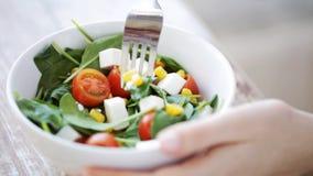 Fermez-vous de la jeune femme mangeant de la salade à la maison banque de vidéos