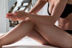 Fermez-vous de la jeune femme sur la plage appliquant la crème photos libres de droits