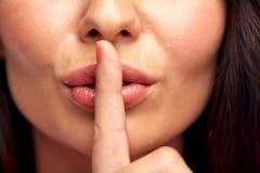 Fermez-vous de la jeune femme tenant le doigt sur des lèvres photo stock