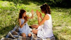 Fermez-vous de la jeune maman attirante et sa de la fille mignonne jouant le jeu de applaudissement banque de vidéos