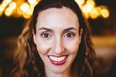 Fermez-vous de la jolie brune souriant à l'appareil-photo Photographie stock