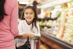 Fermez-vous de la mère poussant la fille dans le chariot à supermarché Photos libres de droits