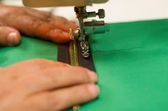 Fermez-vous de la machine à coudre avec une tirette brune sur un tissu vert, aide de mains Photographie stock