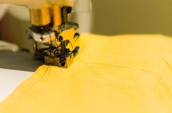 Fermez-vous de la machine à coudre, tissu jaune avec le fil noir Image stock