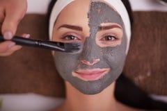 Fermez-vous de la main appliquant le masque facial au visage de femme au salon de beauté image libre de droits