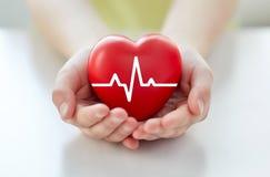 Fermez-vous de la main avec le cardiogramme sur le coeur rouge photo stock