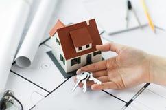 Fermez-vous de la main avec les clés et le modèle de maison Photo stock