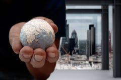 Fermez-vous de la main d'homme d'affaires montrant à texture le concept du monde Photographie stock libre de droits