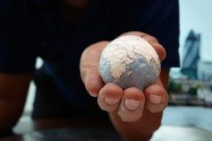 Fermez-vous de la main d'homme d'affaires montrant à texture le monde Photographie stock libre de droits