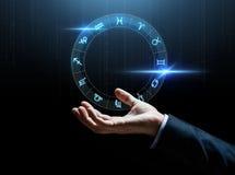 Fermez-vous de la main d'homme d'affaires avec des signes de zodiaque photo stock