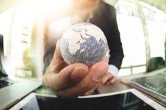 fermez-vous de la main d'homme d'affaires montrant à texture le concept E du monde Photographie stock