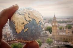 Fermez-vous de la main d'homme d'affaires montrant à texture le monde Photos libres de droits