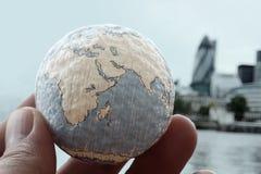 Fermez-vous de la main d'homme d'affaires montrant à texture le monde Photos stock