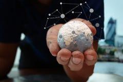 Fermez-vous de la main d'homme d'affaires montrant à texture le monde Photo stock