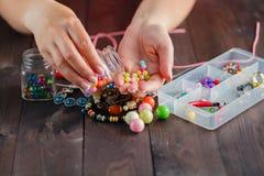 Fermez-vous de la main de femme filetant des perles Photos stock