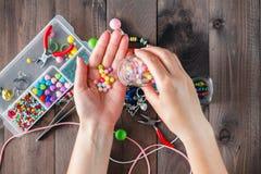 Fermez-vous de la main de femme filetant des perles Photo libre de droits