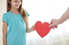 Fermez-vous de la main de fille et de mâle tenant le coeur rouge Photo stock