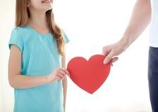 Fermez-vous de la main de fille et de mâle tenant le coeur rouge Images stock