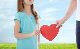 Fermez-vous de la main de fille et de mâle tenant le coeur rouge Photos libres de droits