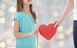 Fermez-vous de la main de fille et de mâle tenant le coeur rouge Photo libre de droits