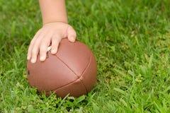 Fermez-vous de la main de l'enfant sur le football photographie stock libre de droits