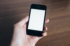 Fermez-vous de la main de l'homme avec le smartphone Photographie stock libre de droits