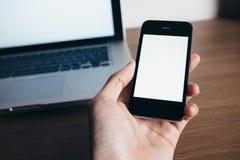 Fermez-vous de la main de l'homme avec le smartphone et l'ordinateur portable Images libres de droits