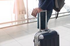 Fermez-vous de la main de l'homme tenant la valise de passeport et de bagage Photo stock