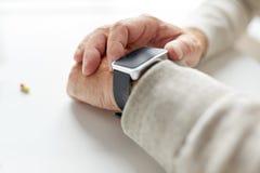 Fermez-vous de la main de vieil homme avec la pilule et la montre intelligente Photographie stock libre de droits