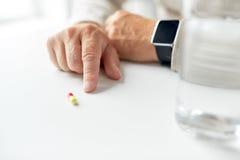 Fermez-vous de la main de vieil homme avec la pilule et la montre intelligente Photos stock
