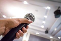 Fermez-vous de la main du ` s de l'homme tenant le microphone dans la salle de conférences ou image stock