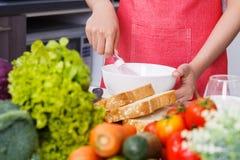 Fermez-vous de la main faisant cuire et battant des oeufs dans une cuvette dans la cuisine Photo stock