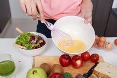 Fermez-vous de la main faisant cuire et battant des oeufs dans une cuvette dans la cuisine Image stock