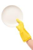 Fermez-vous de la main femelle dans le gant en caoutchouc protecteur jaune tenant le plat blanc propre contre le blanc Photos libres de droits