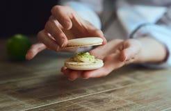 Fermez-vous de la main femelle de chef de pâtisserie faisant cuire le macaron délicieux photo stock