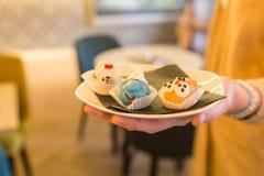 Fermez-vous de la main femelle qui tiennent le plat avec les gâteaux faits maison en Th Photo libre de droits