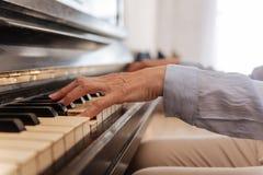 Fermez-vous de la main femelle tout en jouant le piano Image libre de droits